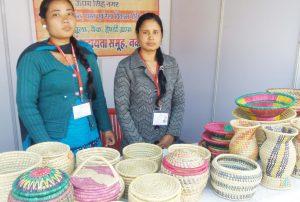 घास से बनी टोकरियां व बर्तन दिखाती युवतियां