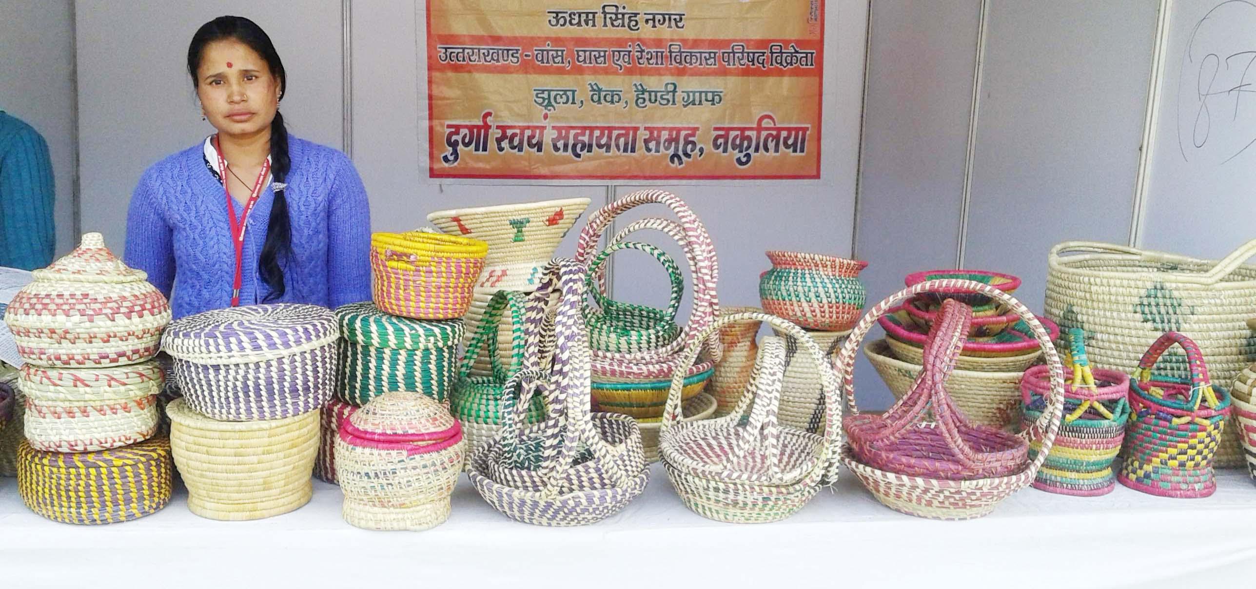 घास से बने उत्पाद दिखाती युवती